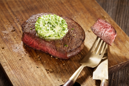 steaks: Steak with green butter on wooden board