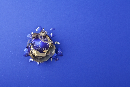 Broken christmas ball on blue background photo