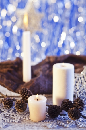 Christmas decorations and candles on blue shiny background photo