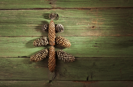 Christmas tree made from fir cones on vintage green wooden background photo