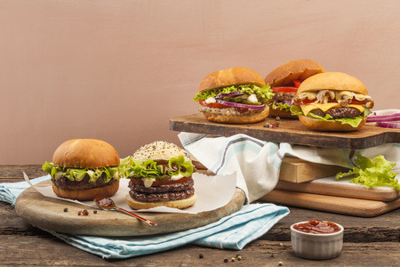 Five different gourmet burgers on wooden background photo
