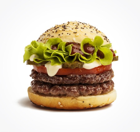 Juicy double burger with pickles, tomatoes and lettuce isolated on white background Фото со стока