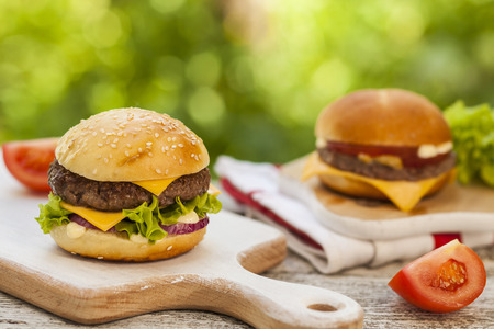 sliders: Tasty burgers with cheese, lettuce, onion and tomatoes served outdoor in summer day