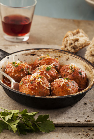Meatballs cooked in tomato sauce in pan on grey backround photo