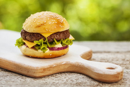 Tasty burger with cheese, lettuce, onion and tomatoes served outdoor on a wooden table  Stock Photo