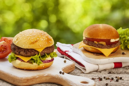 sliders: Tasty burger with cheese, lettuce, onion and tomatoes served outdoor on a wooden table  Stock Photo