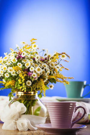 Tea and beautiful wildflowers on wooden background