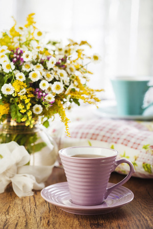 Tea and beautiful wildflowers on wooden background photo