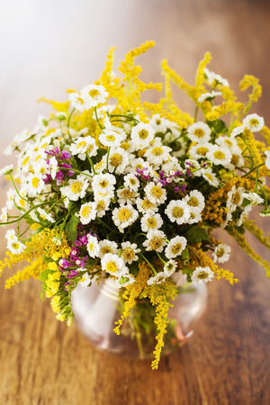 Wildflowers bouquet in glass vase on wooden background photo