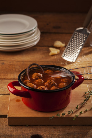 cooked pepper ball: Meatballs closeup in a red casserole on wooden background