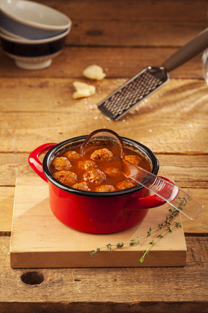 Meatballs closeup in a red casserole on wooden background photo