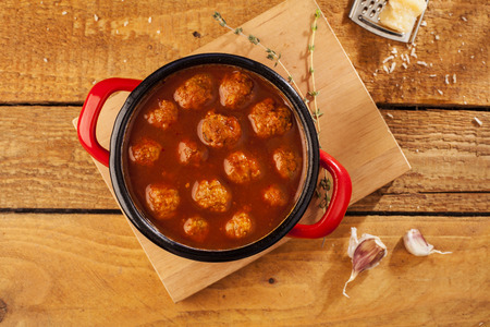 red braised: Meatballs closeup in a red casserole on wooden background