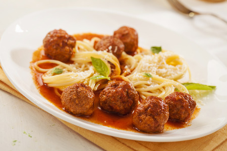 Pasta with meatballs and basil with tomato sauce photo