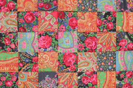 close up of  square fabrics pieced together into a quilt