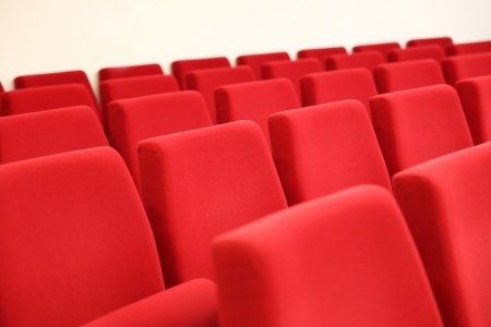 rows of red velvet seats in a big hall