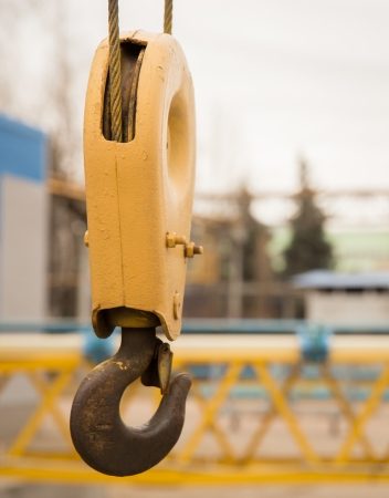 construction tools: yellow crane hook with some industrial buildings on the background Stock Photo