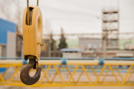 crane parts: yellow crane hook with some industrial buildings on the background Stock Photo
