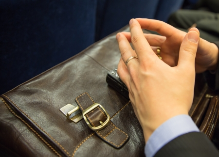 businessman crossed his hands on briefcase during meeting