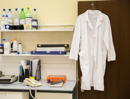 white robe hanging on a door in laboratory Stock Photo