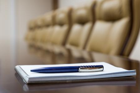sala de reuniones: Primer plano de bloc de notas mantuvo en la mesa en la sala de conferencias vacía