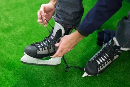 man sitting and preparing for ice skating