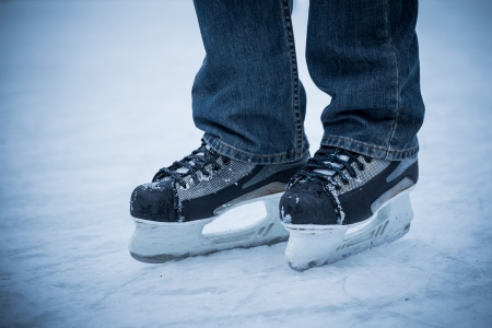 man wearing hockey skaters on ice rink Stock Photo
