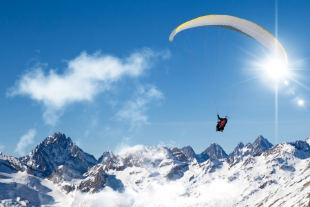 two people paragliding in tandem high in the blue sky