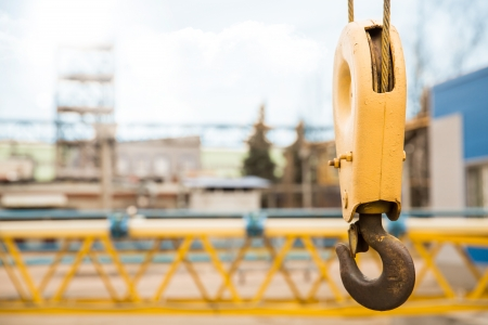 yellow crane hook with some industrial buildings on the background Stock Photo