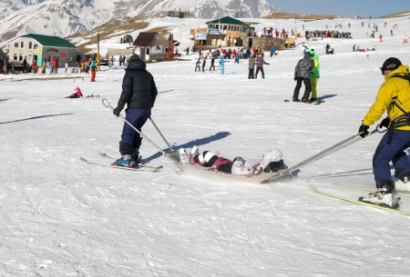 skiing accident: Two members of a ski patrol helping an injured skier down the mountain
