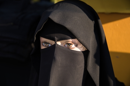 purdah: a mannequin wearing muslim traditional black clothing showing only eyes