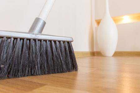 brooming: Sweeping dust with black broom on a wooden floor