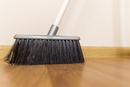 Sweeping dust with black broom on a wooden floor photo