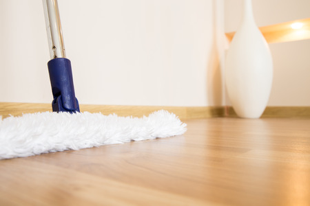 clean house: Modern white mop cleaning wooden floor from dust