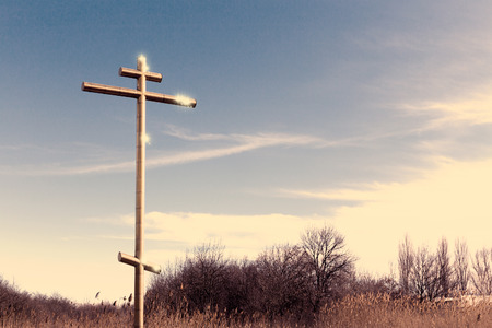 Big golden cross on a roadside with blue sky photo