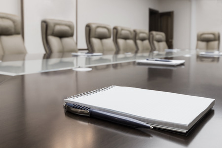 Closeup of notepad kept on table in empty conference room Stock Photo - 26404513