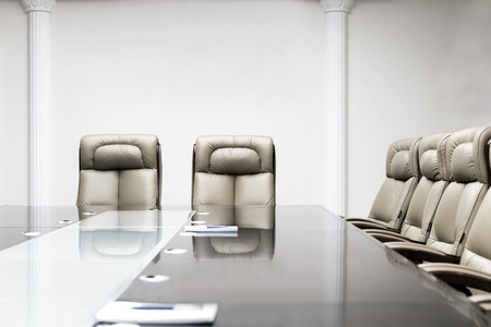 conference room with wooden table and beige leather armchairs