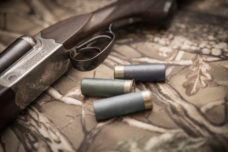 A wooden retro shotgun with shotgun shells
