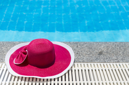 pink hat: Nice pink hat with a bow near the pool