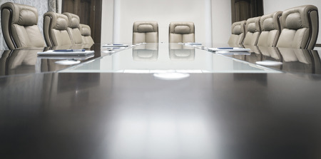 vergaderzaal met houten tafel en beige lederen fauteuils Stockfoto