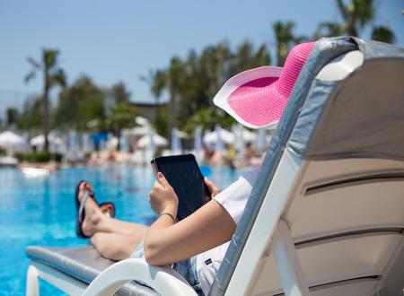 woman on sunbed waering beautiful pink hat photo