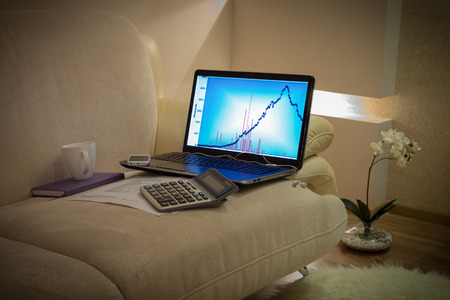 working place with compute and telephone on a couch photo
