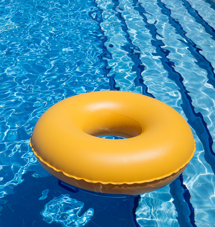aufblasbare gelbe Innenrohr schwebend in klaren blauen Wasser Standard-Bild