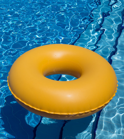 inflatable yellow inner tube floating in clear blue waters photo