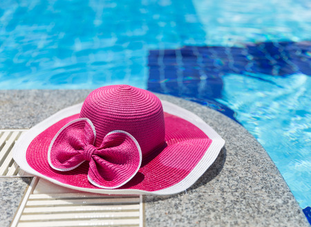 Nice pink hat with a bow near the pool