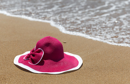 pink hat: Pink hat on the sandy beach of the sea