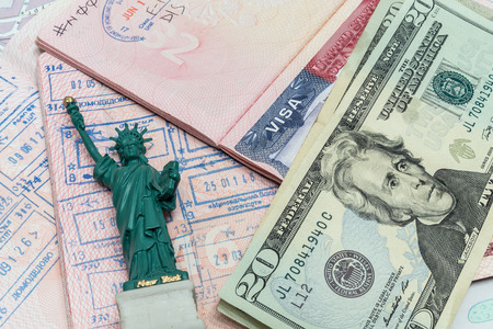 Passport, money and small statue of liberty photo