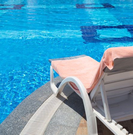 Sunbed covered with towel on edge of a pool photo