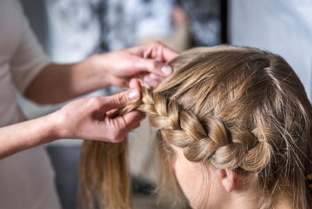 Hairdresser make braid in beauty salon Stock Photo