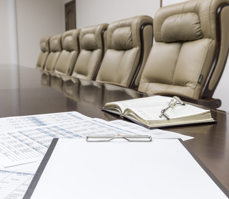 board room: Closeup of  on table in empty corporate conference room before business meeting in office