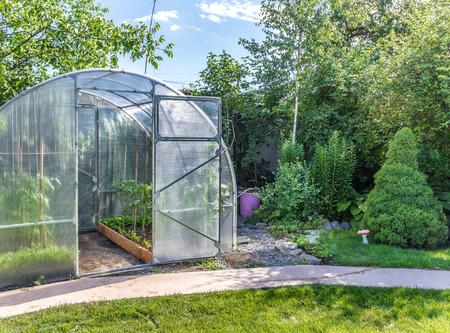 Gewächshaus im Garten hinter dem Haus mit offener Tür Standard-Bild - 33544849